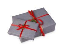 Contenitori di regalo di Natale in carta grigia isolata su bianco Immagine Stock
