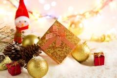 Contenitori di regalo di Natale dell'oro con il pupazzo di neve e la bagattella su neve nell'accensione variopinta Fotografia Stock