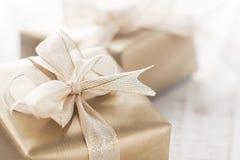 Contenitori di regalo dorati con il bei nastro ed arco su un fondo brillante luminoso Fotografie Stock