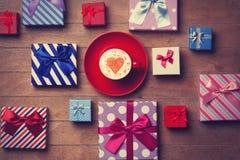 Contenitori di regalo e di tazza su fondo di legno Fotografia Stock