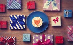 Contenitori di regalo e di tazza su fondo di legno Immagini Stock