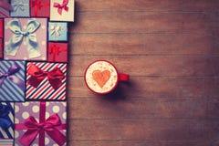 Contenitori di regalo e di tazza su fondo di legno Immagine Stock