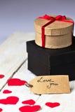 Contenitori di regalo e papercut del cuore su fondo di legno Fotografia Stock