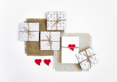 Contenitori di regalo fatti a mano rustici su fondo bianco decorato con i cuori Vista superiore, disposizione piana Immagine Stock Libera da Diritti