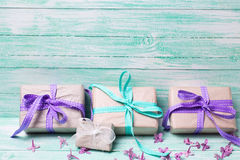 Contenitori di regalo festivi e fiori lilla sul backgr di legno del turchese Fotografie Stock