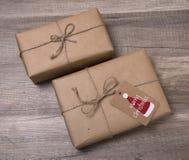 Contenitori di regalo di Natale avvolti in carta kraft, con l'etichetta in bianco del regalo Immagine Stock