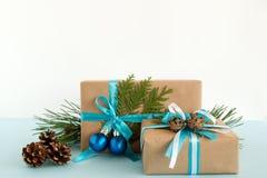 Contenitori di regalo di Natale avvolti dei nastri blu e bianchi della carta del mestiere, decorati dei rami dell'abete, delle pi Fotografia Stock