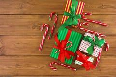 Contenitori di regalo di Natale, caramella su fondo rustico I presente decorati con il nastro rosso e verde si piega Vista superi Fotografie Stock