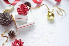 Contenitori di regalo di Natale con un arco rosso, accanto alla palla di Natale, nastro rosso, coni su un fondo bianco con neve fotografia stock