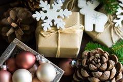 Contenitori di regalo, Natale, nuovo anno, bagattelle variopinte in scatola di legno, pigne, rami di albero dell'abete, ornamenti Immagini Stock