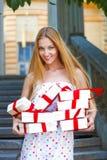 Contenitori di regalo nelle mani di giovane donna bionda Immagine Stock