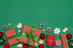 Contenitori di regalo, palle di Natale, giocattoli, coni di abete, nastro su fondo verde Festivo, congratulazione, regali di Nata immagine stock libera da diritti