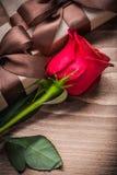 Contenitori di regalo rossi fioriti del bocciolo di rosa sul concetto di festa del bordo di legno Immagine Stock