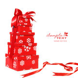 Contenitori di regalo rossi impilati con il nastro rosso Immagine Stock