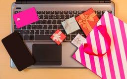 Contenitori di regalo, sacchetto della spesa, carta di credito e smartphone sulla tastiera del computer portatile Fotografia Stock