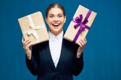 Contenitori di regalo sorridenti felici della tenuta della donna di affari Fotografia Stock