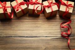 Contenitori di regalo su fondo di legno, presente del cartone di festa Fotografia Stock