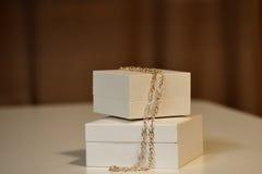 Contenitori di regalo su una tavola con una catena dell'oro Fotografia Stock