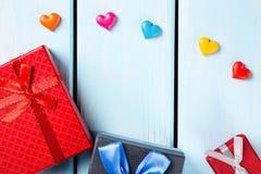 Contenitori di regalo variopinti con i cuori decorativi su fondo di legno blu piacevole Fotografia Stock