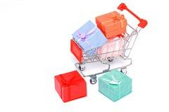 Contenitori di regalo variopinti con il carrello di acquisto isolato Fotografie Stock