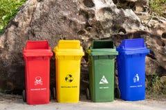 Contenitori di rifiuti colorati differenti per la separazione dell'immondizia con il segno e l'icona vicino alla spiaggia per il  immagine stock