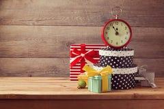 Contenitori ed orologio di regalo sulla tavola di legno Concetto di celebrazione del nuovo anno Fotografia Stock Libera da Diritti