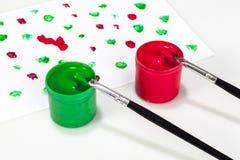 Contenitori rossi e verdi di pittura con le spazzole Immagine Stock