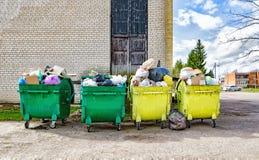 Contenitori verdi e gialli con immondizia vicino alla casa Fotografia Stock Libera da Diritti