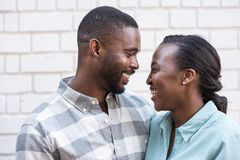 Content African couple smiling at each other in the city. Smiling young African couple looking into each other`s eyes while standing together in front of a brick Royalty Free Stock Photos