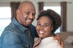 Content African couple smiling while standing together at home. Portrait of an affectionate African couple smiling and hugging each other while standing together stock photo