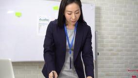 Content Asian Business, poprawiająca dokumenty, stojąc przy stole biurowym zbiory wideo