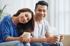 Wonderful young ethnic couple with mugs royalty free stock photography