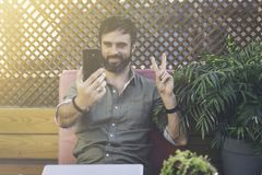Content attractive man in stylish clothes photographing himself on mobile phone and showing peace gesture.Bearded. Hipster making selfie via smartphone on royalty free stock photos