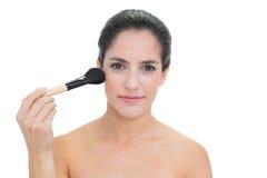 Content bare brunette holding powder brush Stock Images