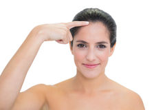 Content bare brunette pointing at forehead Stock Photography