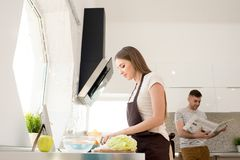 Pretty girl in apron cutting vegetable in kitchen stock photography