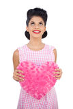 Content black hair model holding a pink heart shaped pillow Stock Image