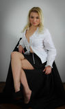 Content. Blond woman in black mini skirt, white shirt and high heels, sitting on a chair smiling content stock images