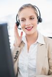 Content blonde call centre agent interacting with customer Stock Images