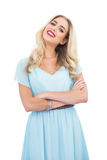 Content blonde model in blue dress posing crossed arms Royalty Free Stock Photo