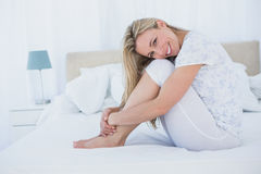 Content blonde sitting in her bed Stock Images