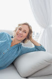 Content blonde woman relaxing on her couch Stock Image
