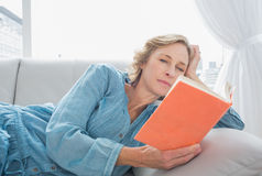 Content blonde woman relaxing on her couch reading book Stock Images