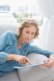 Content blonde woman relaxing on her couch using her tablet Royalty Free Stock Photography