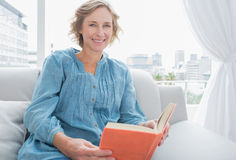 Content blonde woman sitting on her couch holding a book Stock Images