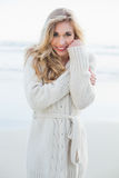 Content blonde woman in wool cardigan looking at camera Royalty Free Stock Photo