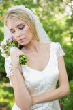 Content bride holding her bouquet wearing a veil Royalty Free Stock Photos