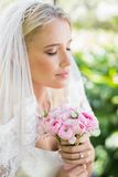 Content bride wearing veil holding bouquet with eyes closed. In the countryside Royalty Free Stock Photography