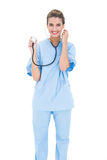 Content brown haired nurse in blue scrubs holding her stethoscope Stock Image