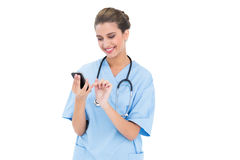 Content brown haired nurse in blue scrubs using a mobile phone Royalty Free Stock Images